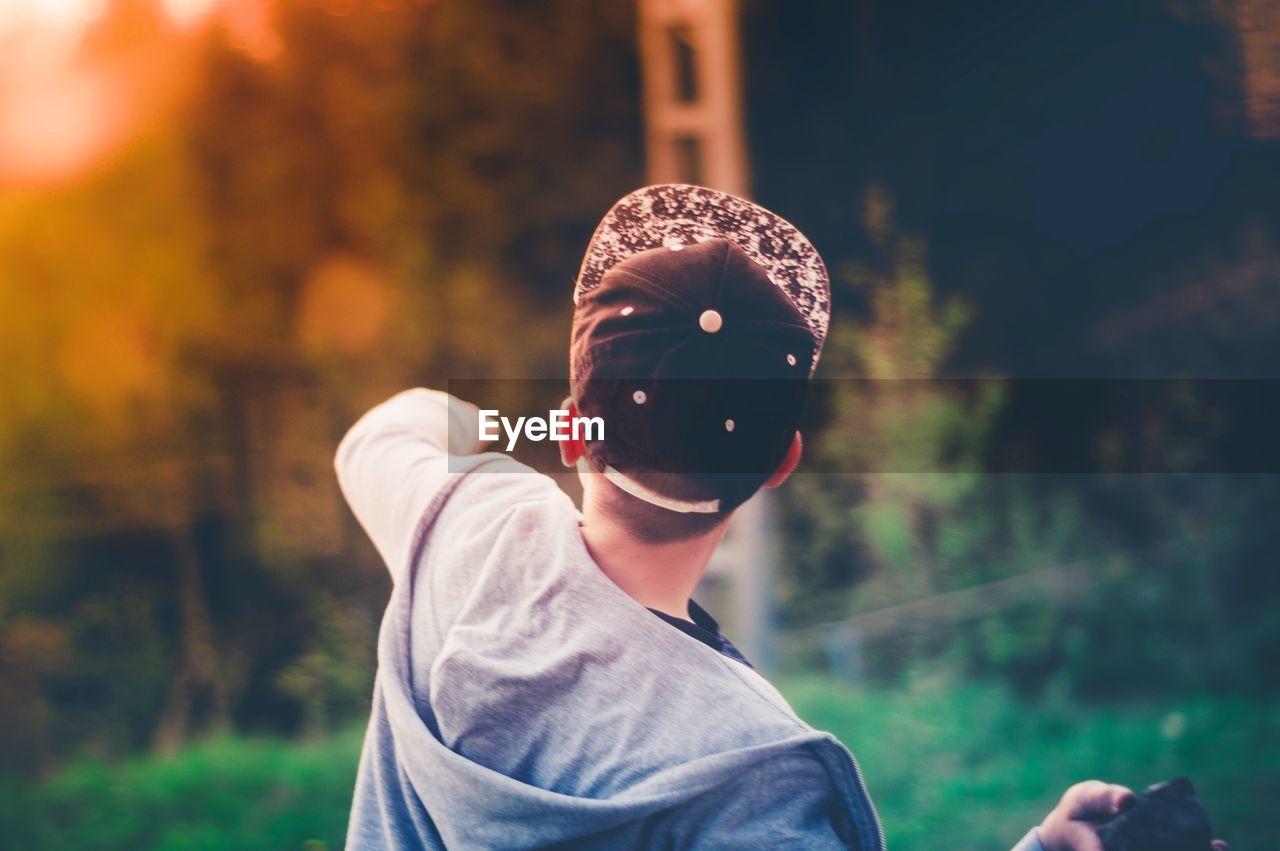 Boy Wearing Baseball Cap Against Trees