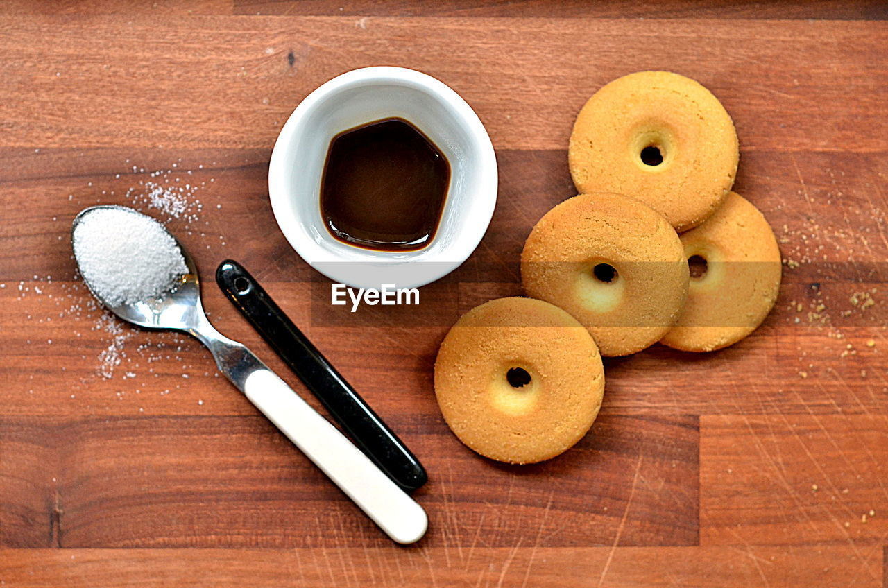 food and drink, table, food, freshness, still life, cookie, indoors, sweet food, wood - material, cutting board, brown, directly above, no people, dessert, ready-to-eat, close-up, donut, day