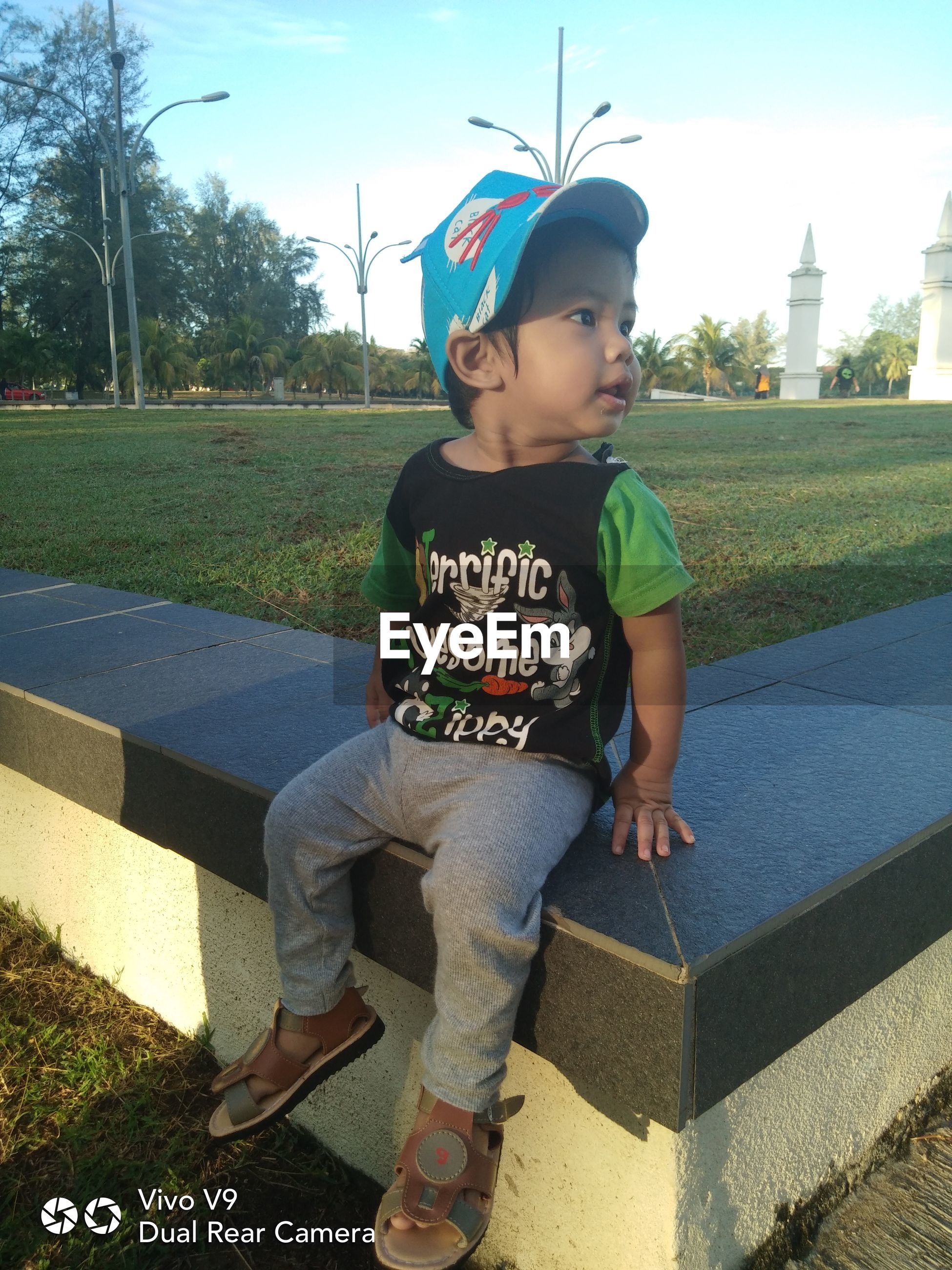 BOY SITTING ON A PARK