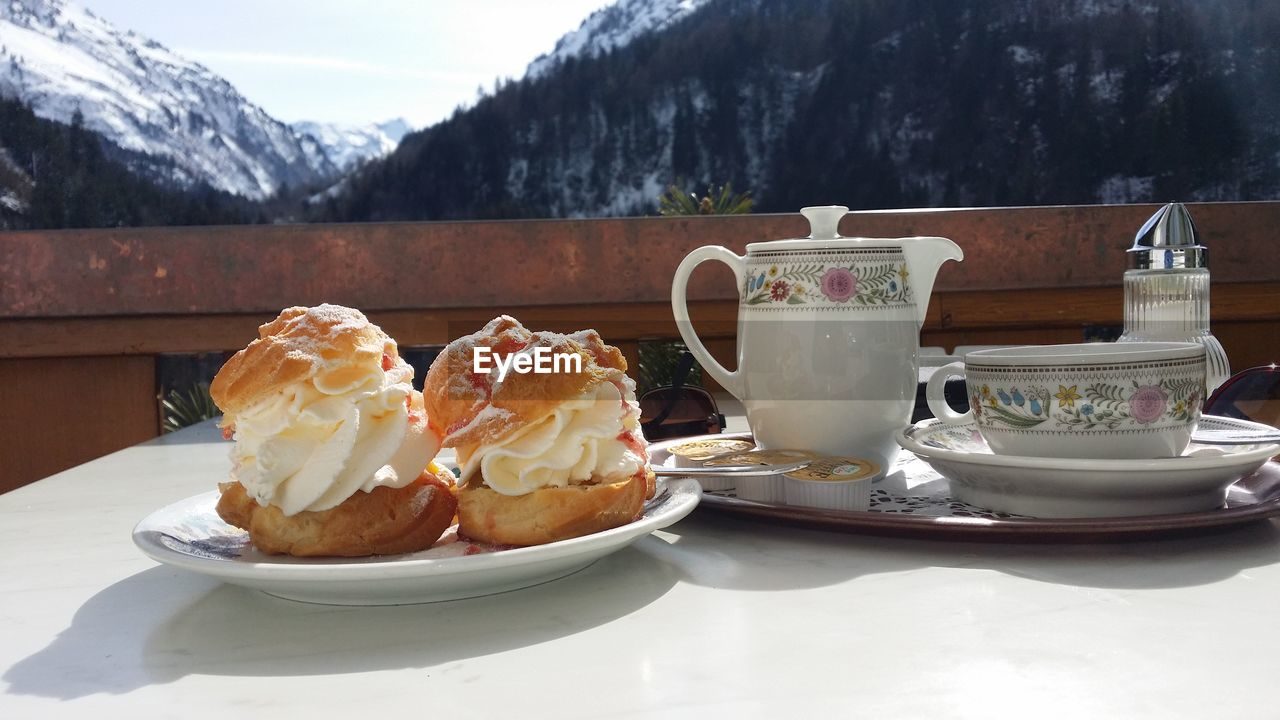 Food In Plate By Cup On Table Against Mountains During Winter