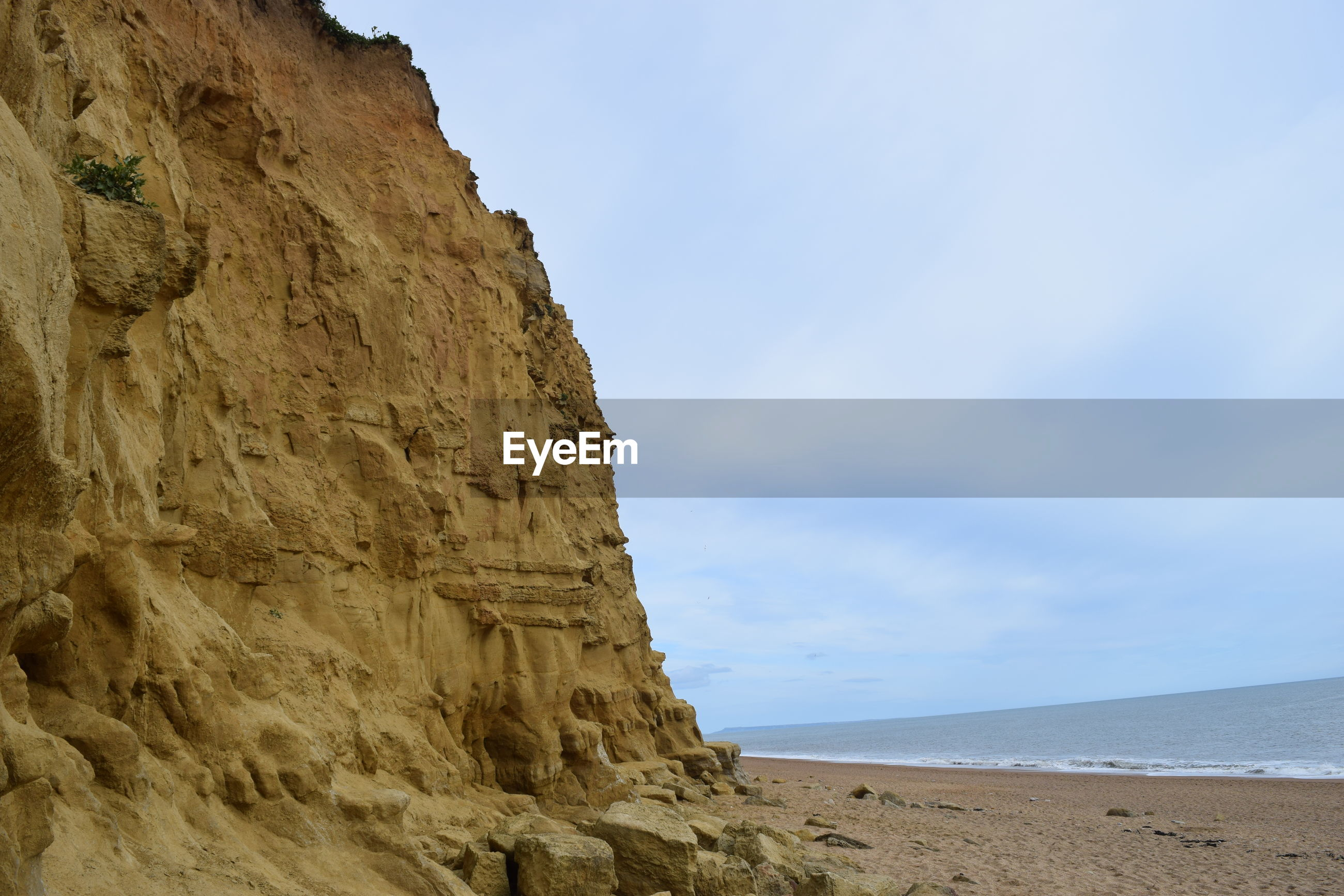 SCENIC VIEW OF ROCK FORMATIONS ON BEACH AGAINST SKY