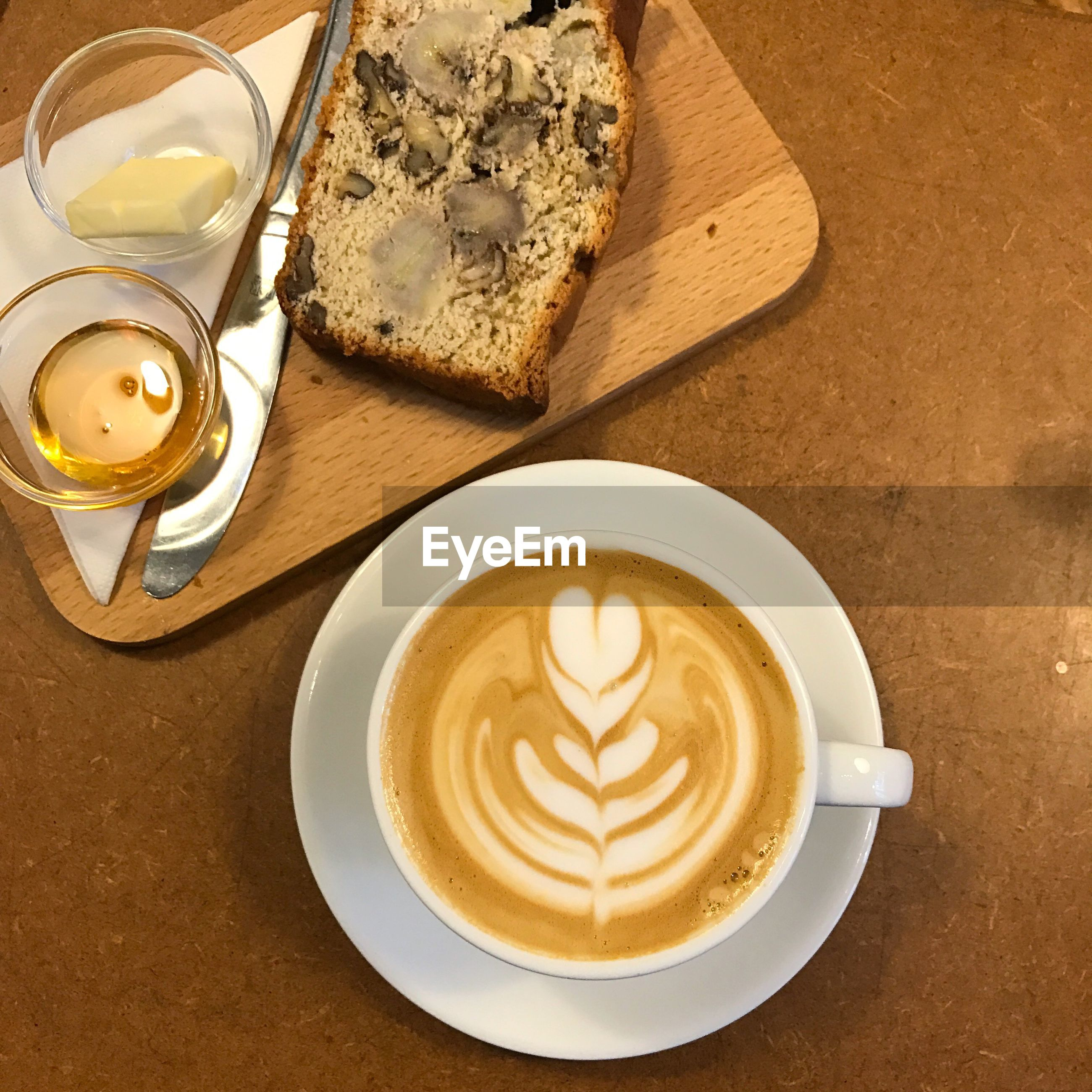 Directly above shot of coffee with bread and ingredients on table