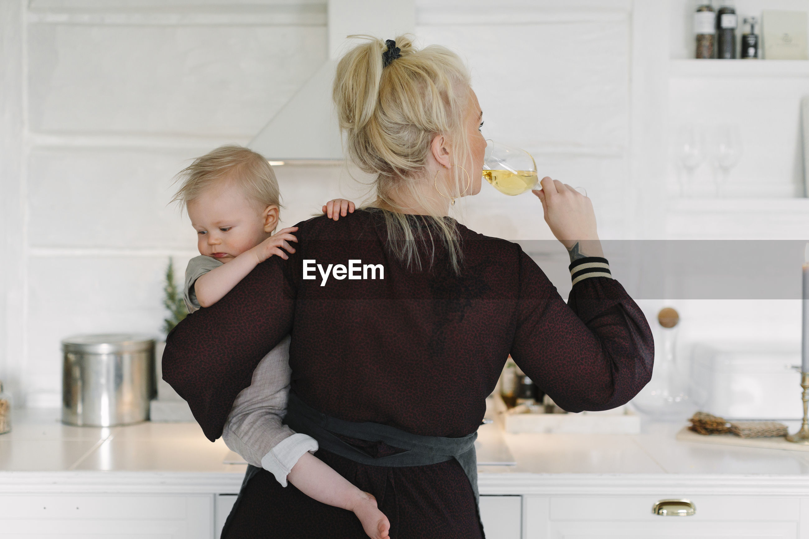 REAR VIEW OF MOTHER AND DAUGHTER IN HOME