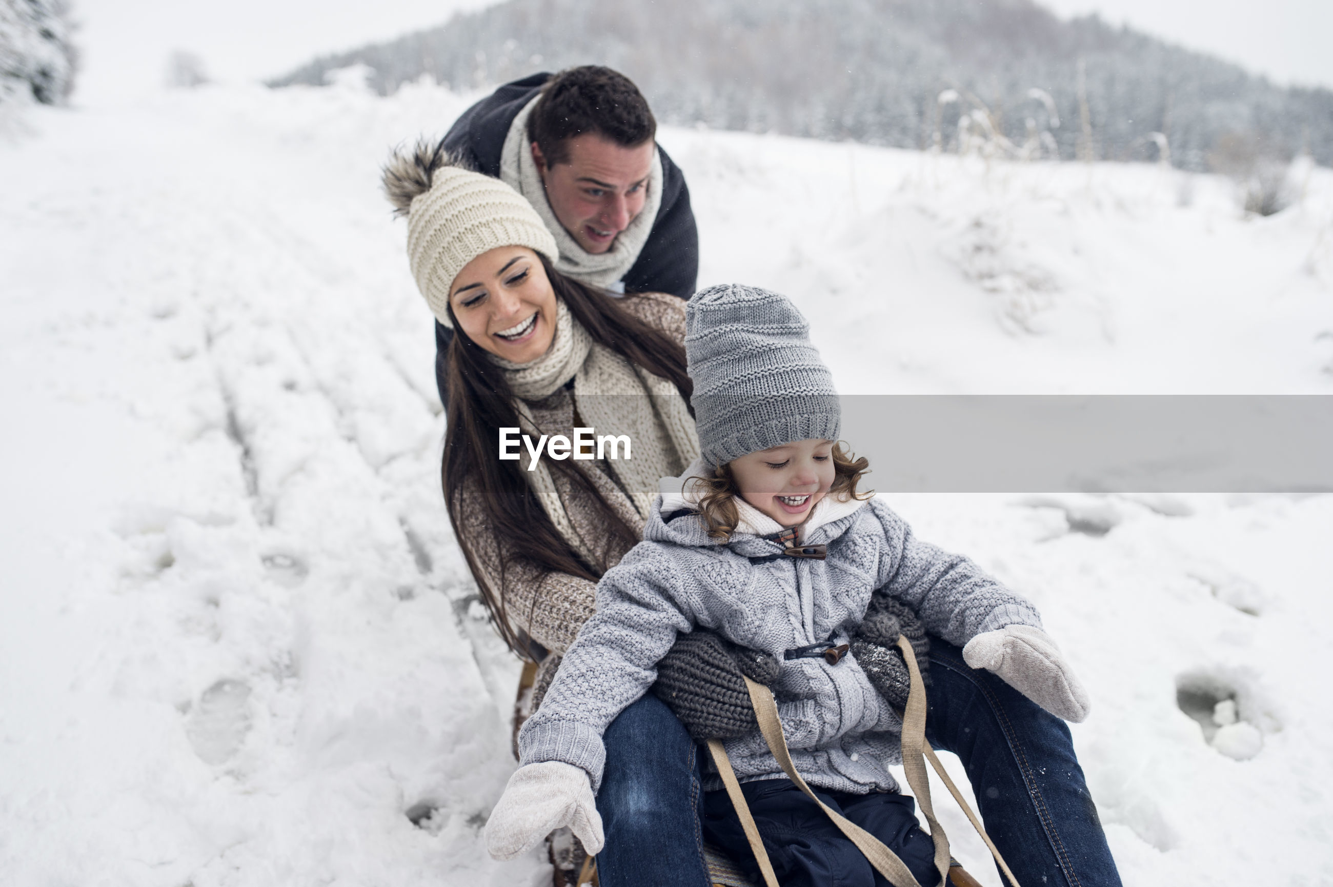 HAPPY MOTHER AND SON ON SNOW DURING WINTER