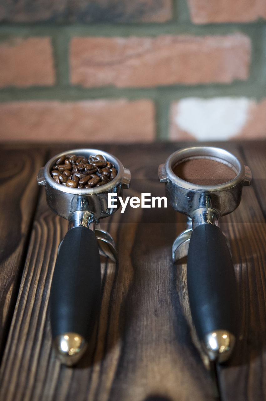 High Angle View Of Coffee In Containers On Table Against Brick Wall In Cafe