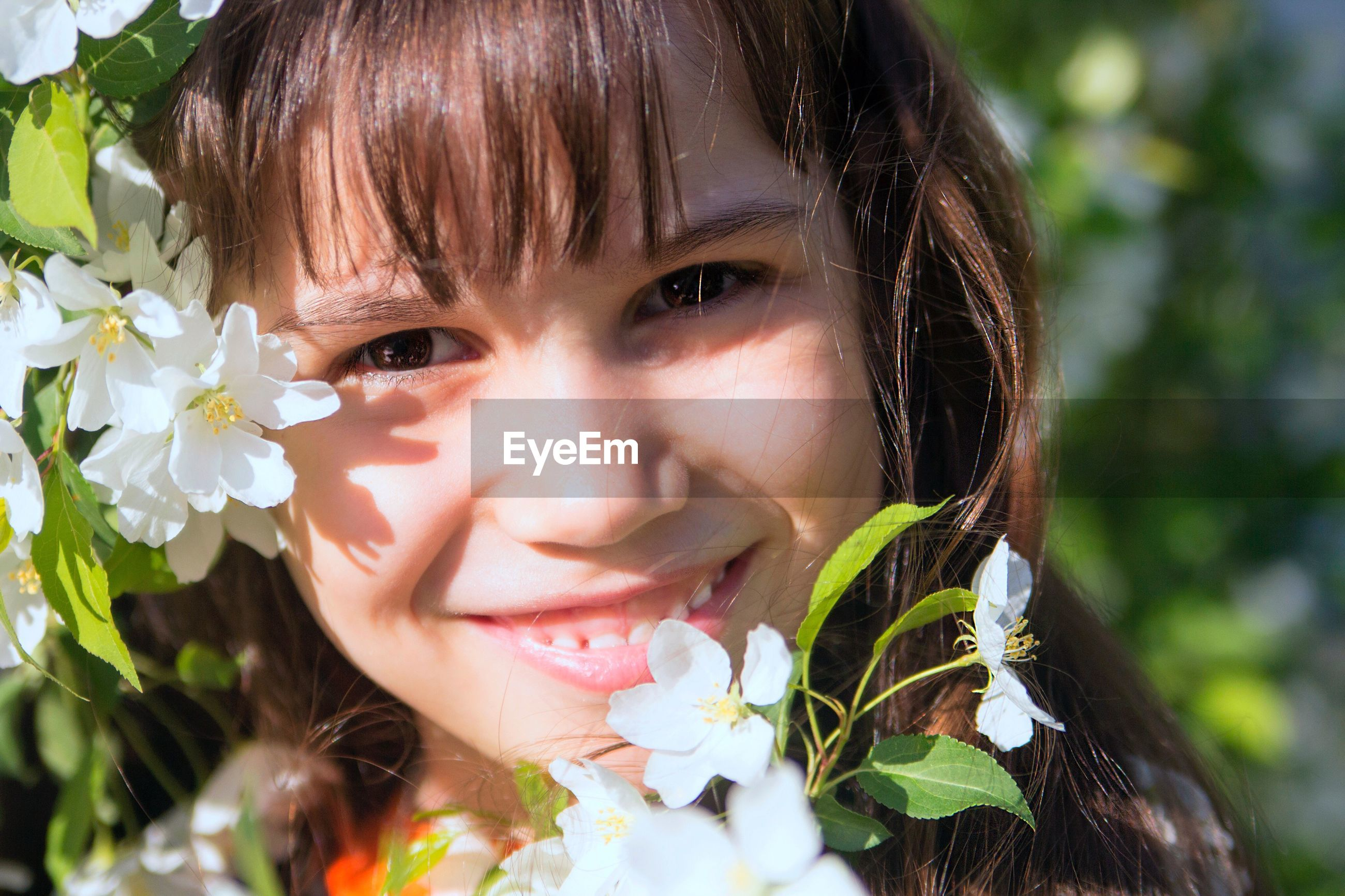 Close-up portrait of cute girl by white flowers blooming outdoors