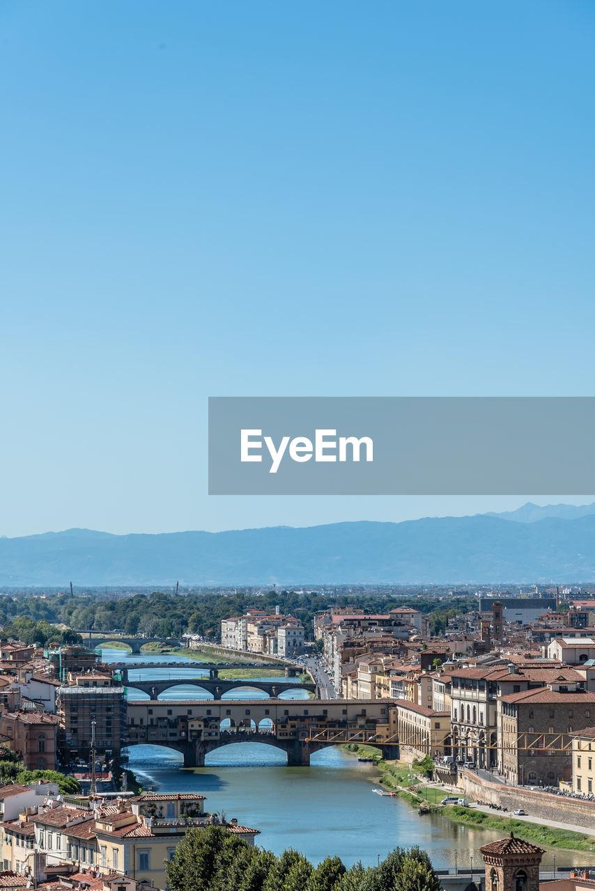 Ponte Vecchio Over Arno River Against Blue Sky In City