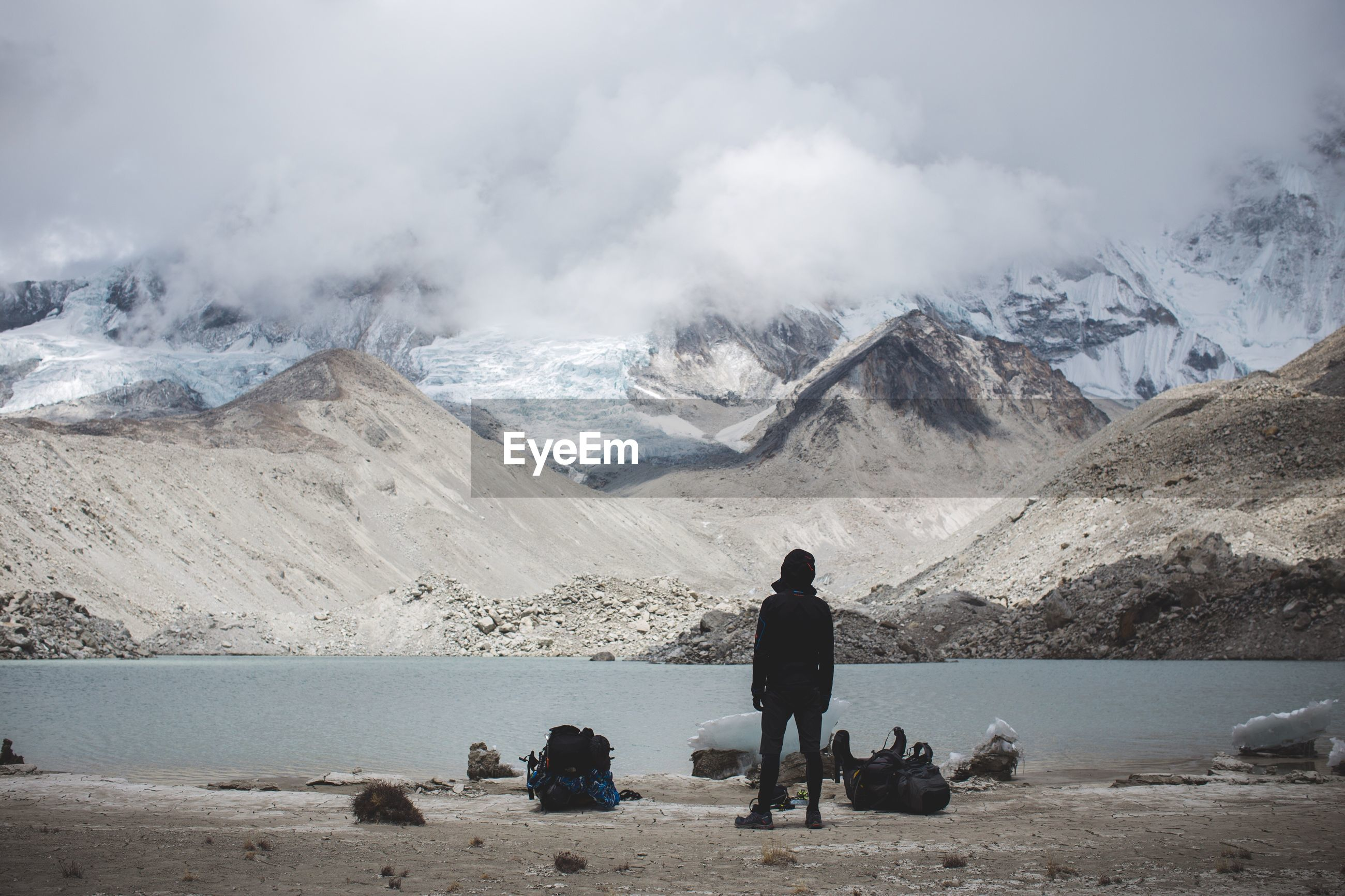Rear view of person standing by river against mountain