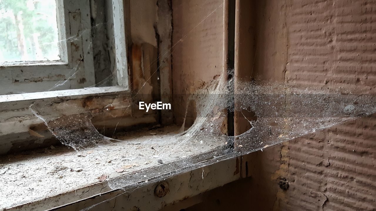 window, architecture, old, built structure, no people, abandoned, day, indoors, wall - building feature, damaged, building, weathered, bad condition, obsolete, spider web, decline, close-up, wood - material, deterioration, window frame, ruined