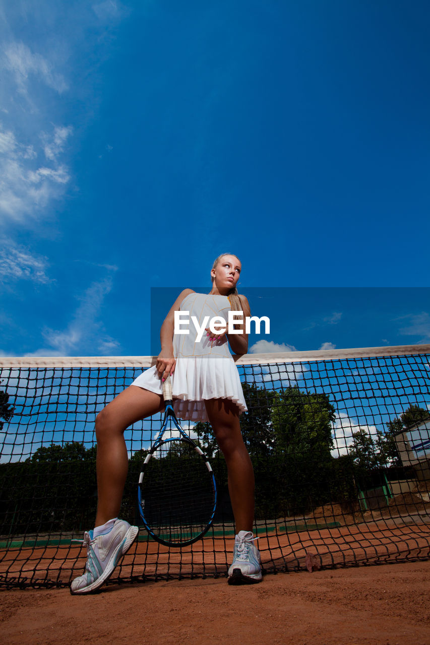 one person, sport, leisure activity, lifestyles, tennis racket, court, real people, racket, tennis, full length, net - sports equipment, blue, sky, ball, playing, day, adult, women, outdoors, skill