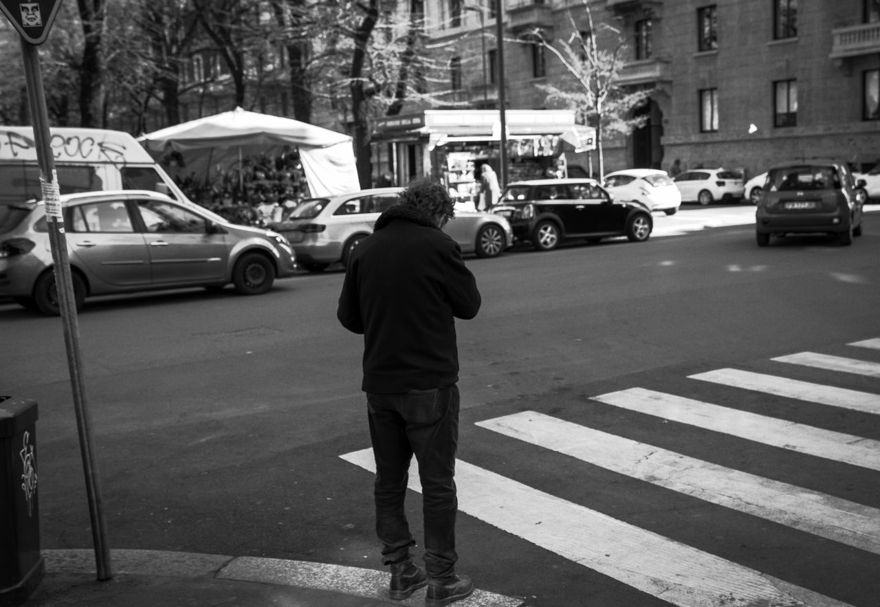 city, car, transportation, motor vehicle, street, mode of transportation, land vehicle, road, real people, one person, rear view, men, crosswalk, zebra crossing, architecture, crossing, building exterior, full length, road marking, city life, city street