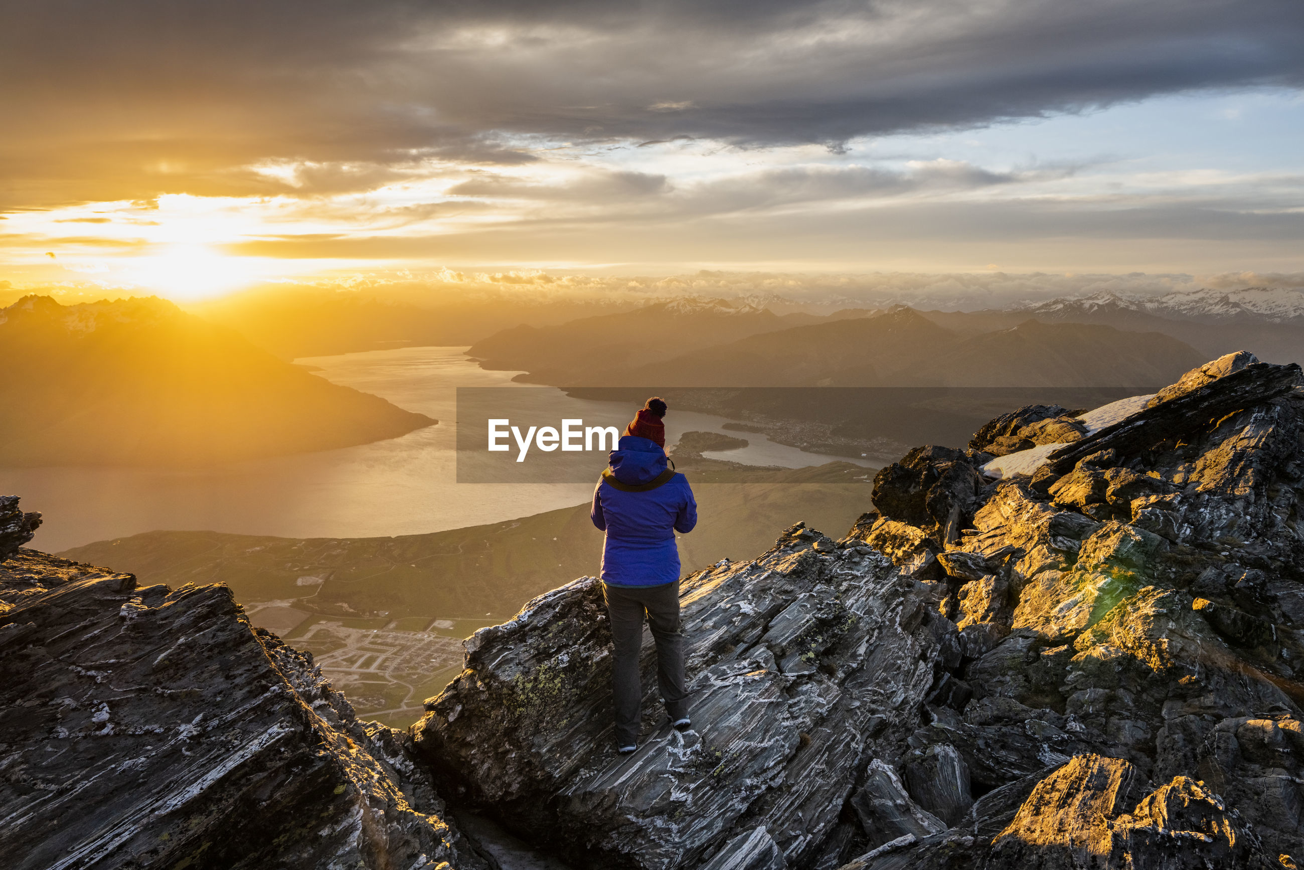 REAR VIEW OF MAN LOOKING AT VIEW OF MOUNTAINS