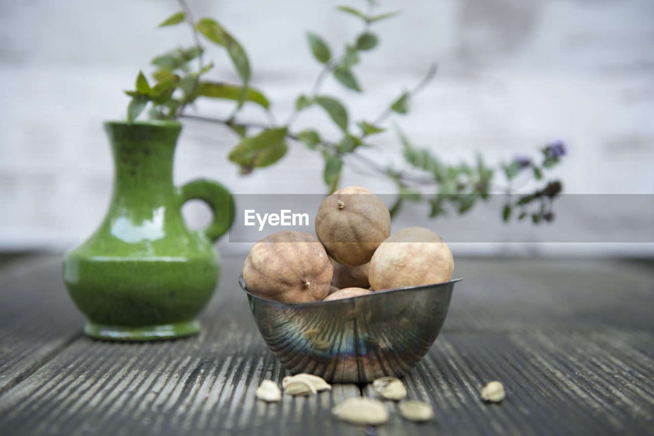 Close-up of dried lemons in bowl with vase on table