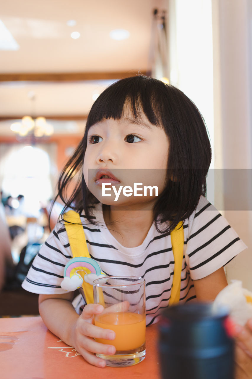 Close-Up Of Girl Looking Away While Having Drink At Table In Restaurant