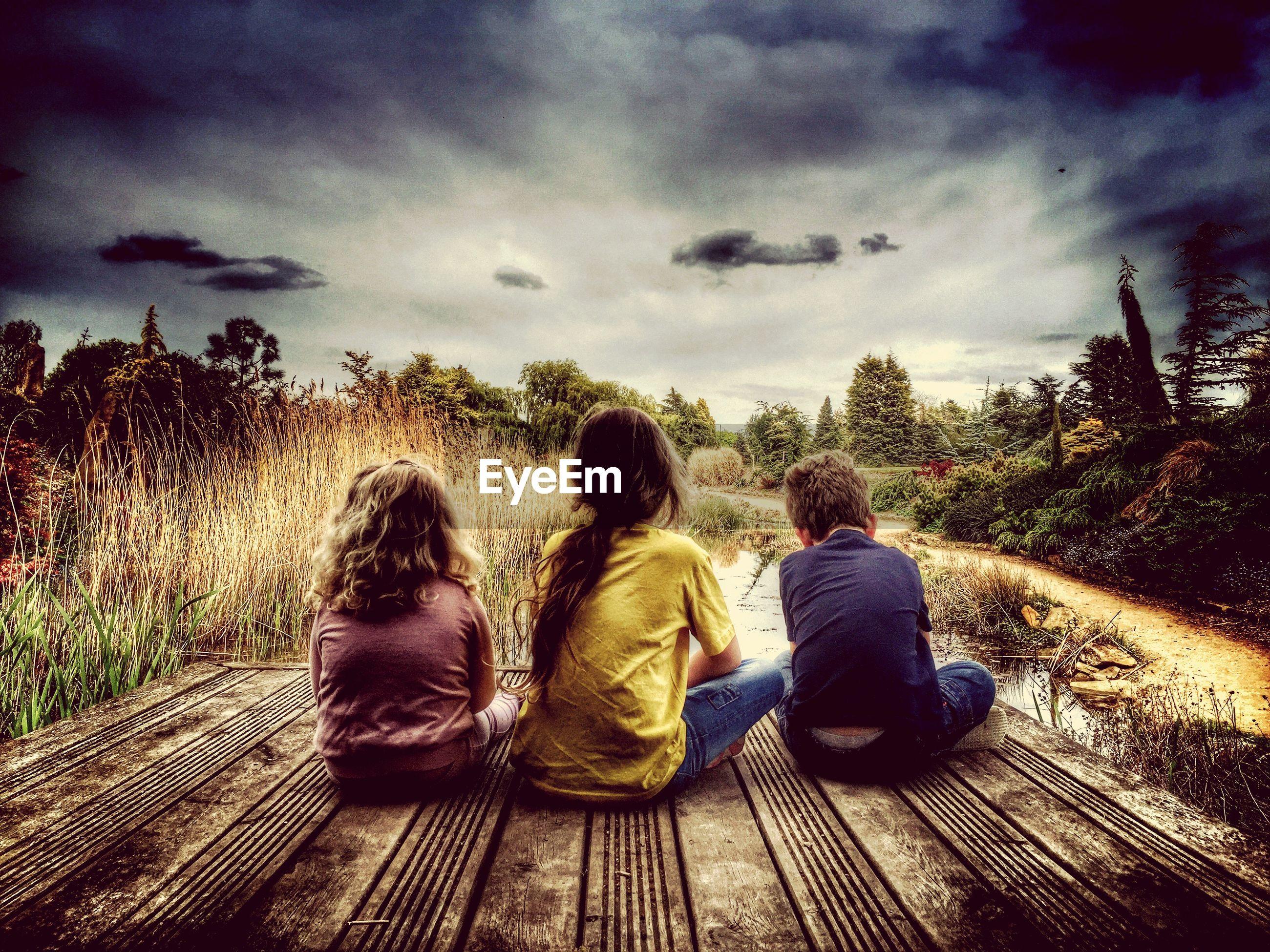 Siblings sitting on boardwalk against cloudy sky