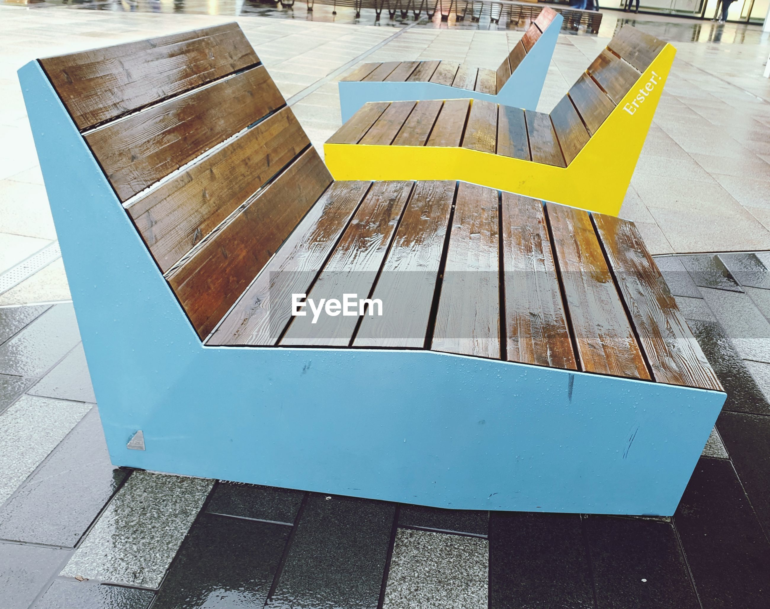 High angle view of empty wooden seats in city