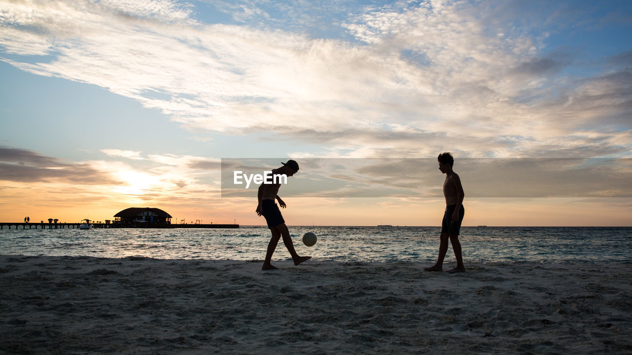 Silhouette People Playing Soccer At Beach Against Sky During Sunset