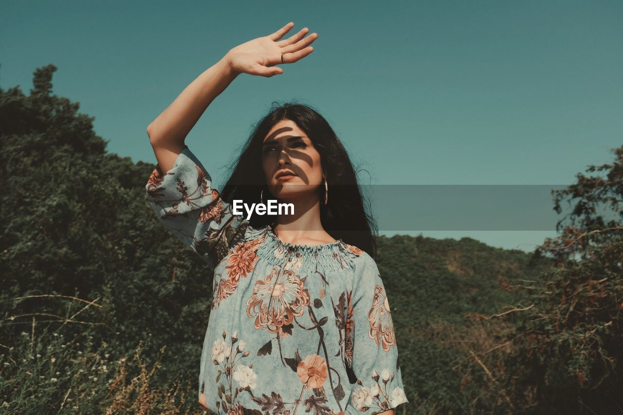 Young Woman Standing Shielding Eyes In Forest