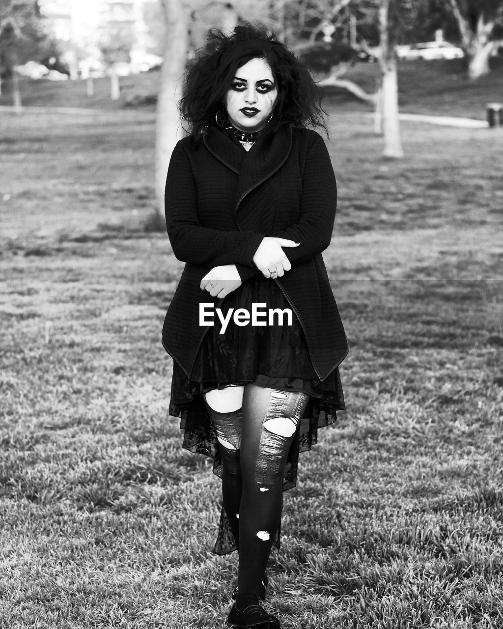 Portrait Of Gothic Woman Walking On Grassy Field