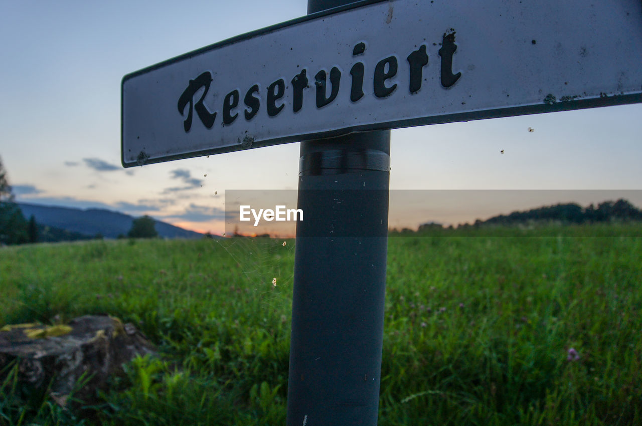 communication, text, sign, western script, grass, field, sky, nature, land, plant, information, focus on foreground, no people, guidance, outdoors, information sign, close-up, day, landscape, green color