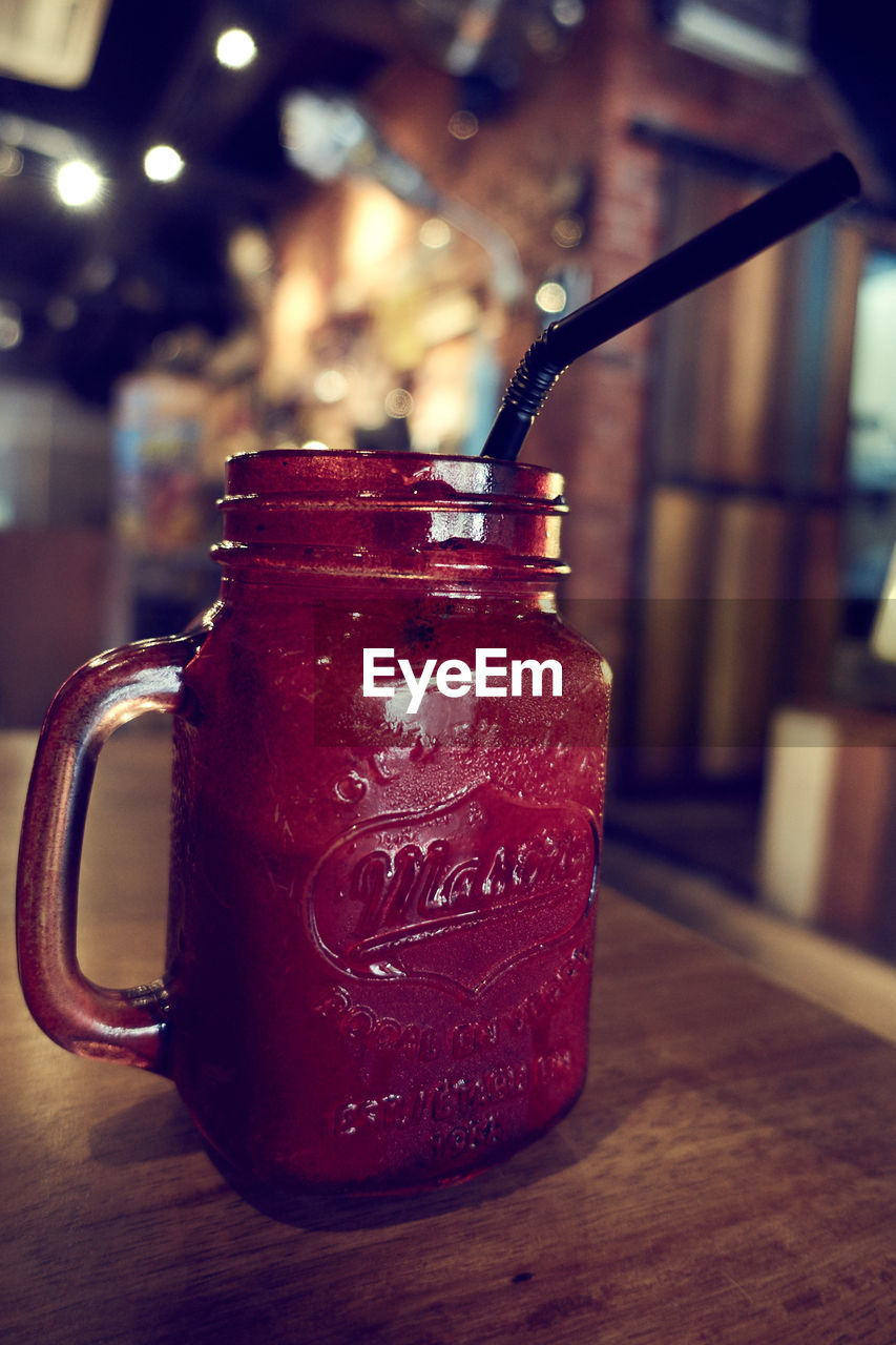 focus on foreground, table, indoors, food and drink, close-up, container, jar, still life, refreshment, drink, no people, red, freshness, cup, food, glass - material, transparent, wood - material, text, handle, glass, non-alcoholic beverage