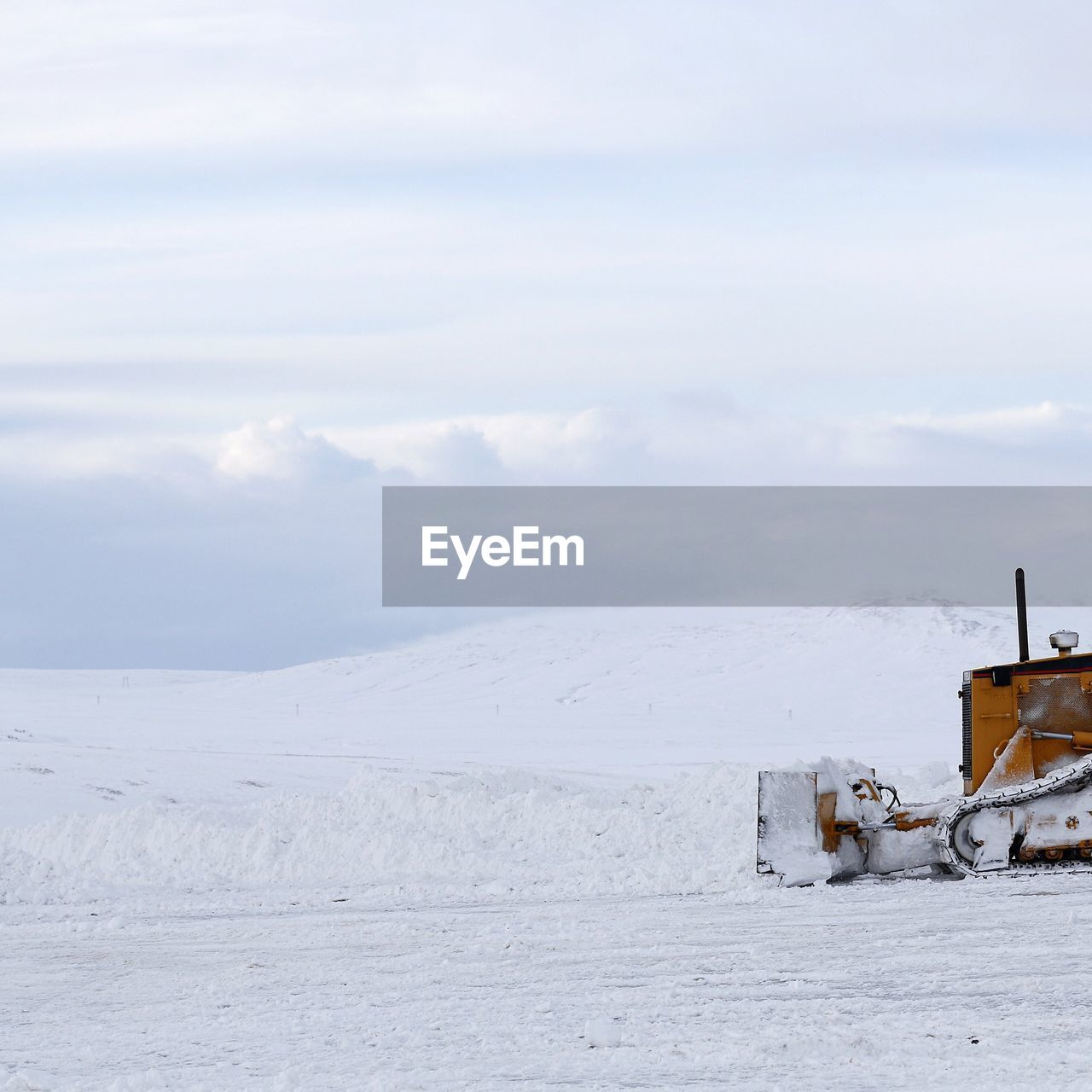 Snowplow on snow covered field against sky