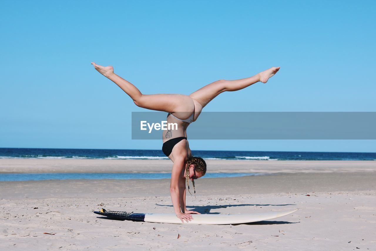 Woman Doing Handstand At Beach Against Clear Sky