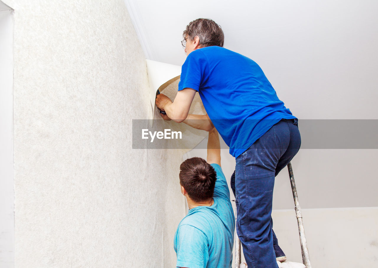 Rear view of father and son applying wallpaper on wall at home