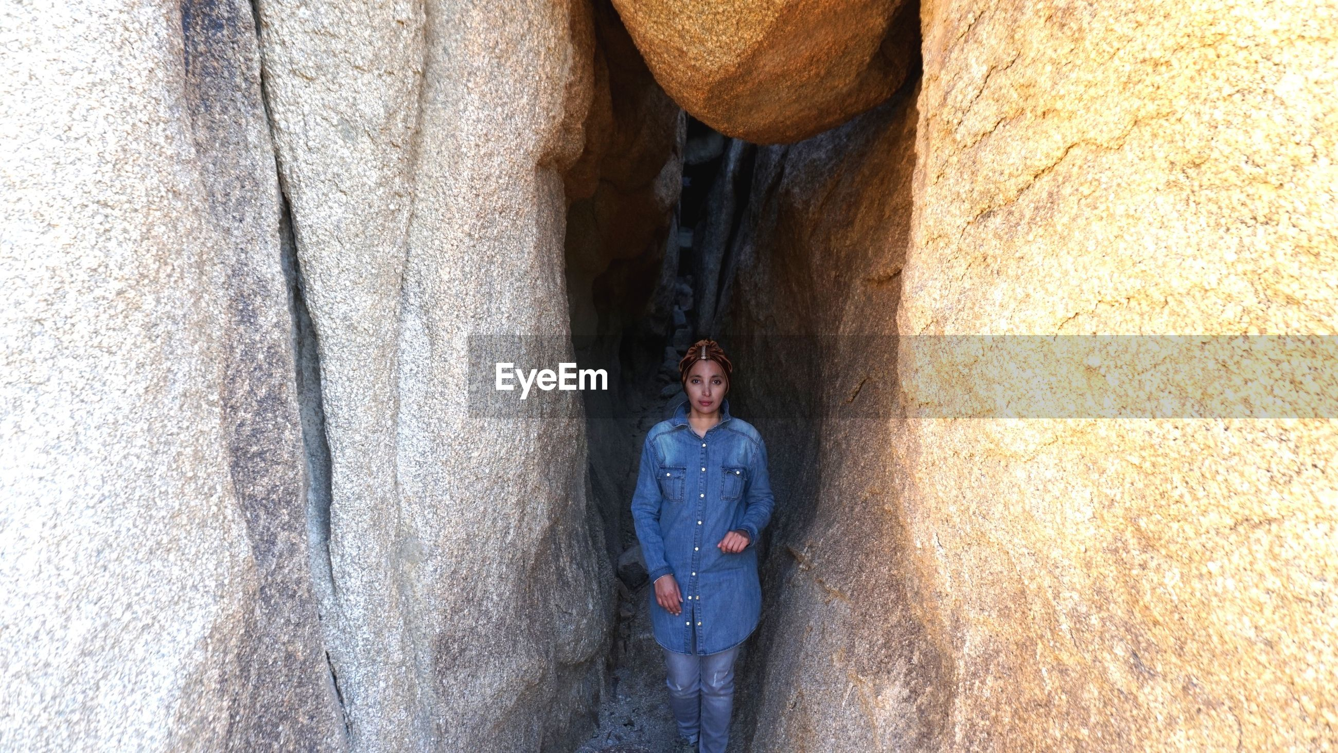 Portrait of mid adult woman standing by rock formations