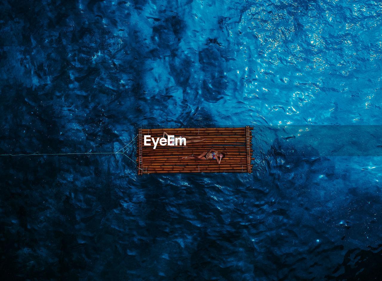 Directly Above Shot Of Bikini Women Lying On Wooden Raft In Sea