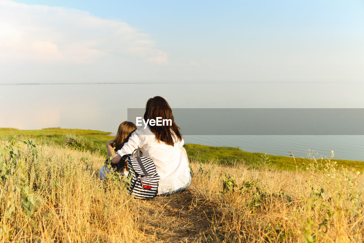 REAR VIEW OF WOMEN ON GRASS AT SHORE