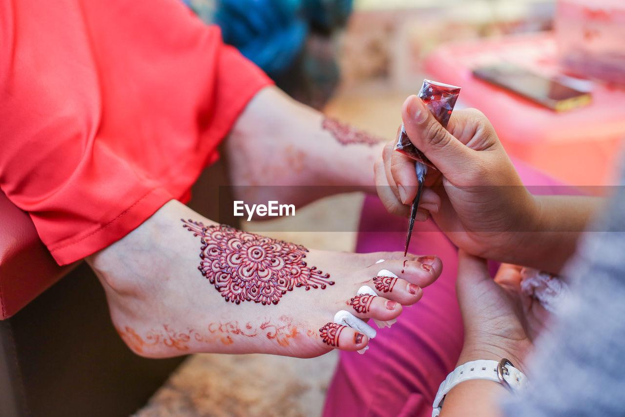 Cropped image of beautician making henna tattoo on bride leg