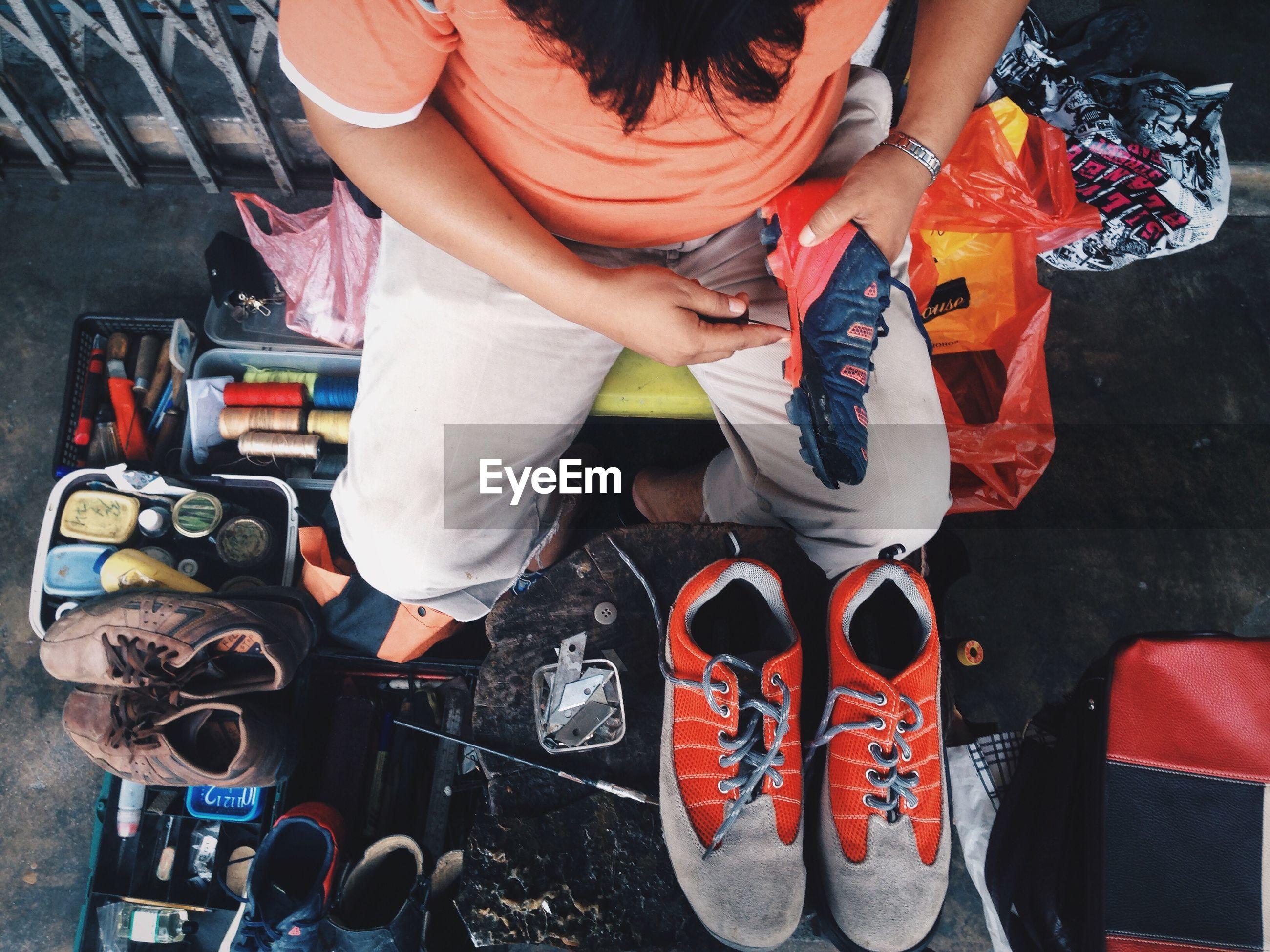 Directly above shot of man stitching shoe