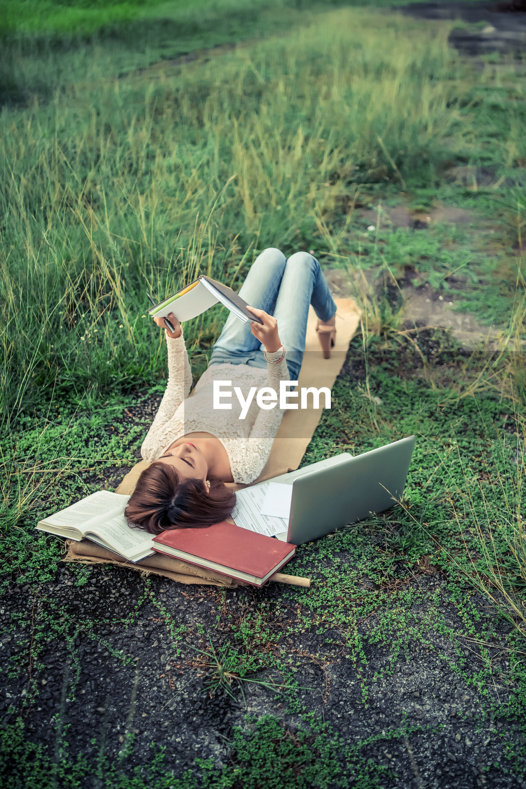 High angle view of young woman reading book while lying on field