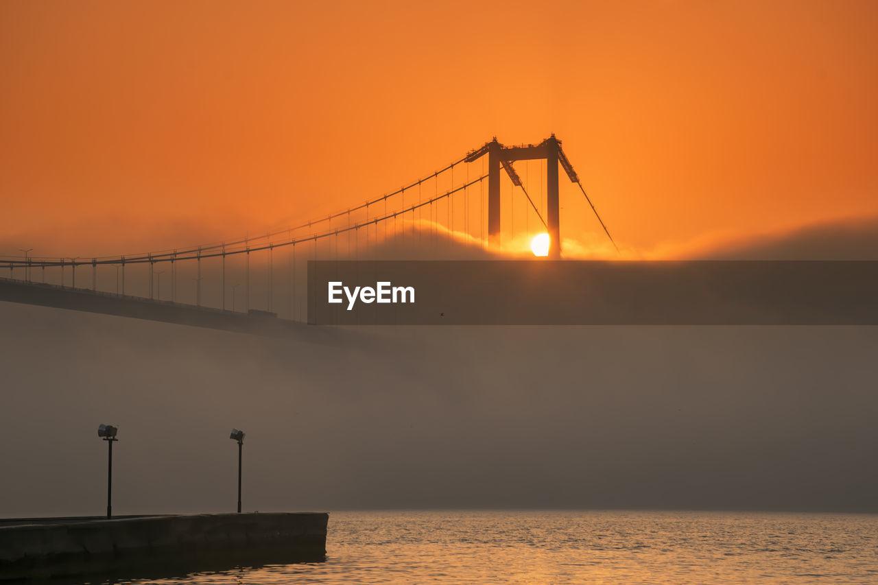 Silhouette bridge over sea against orange sky and fog