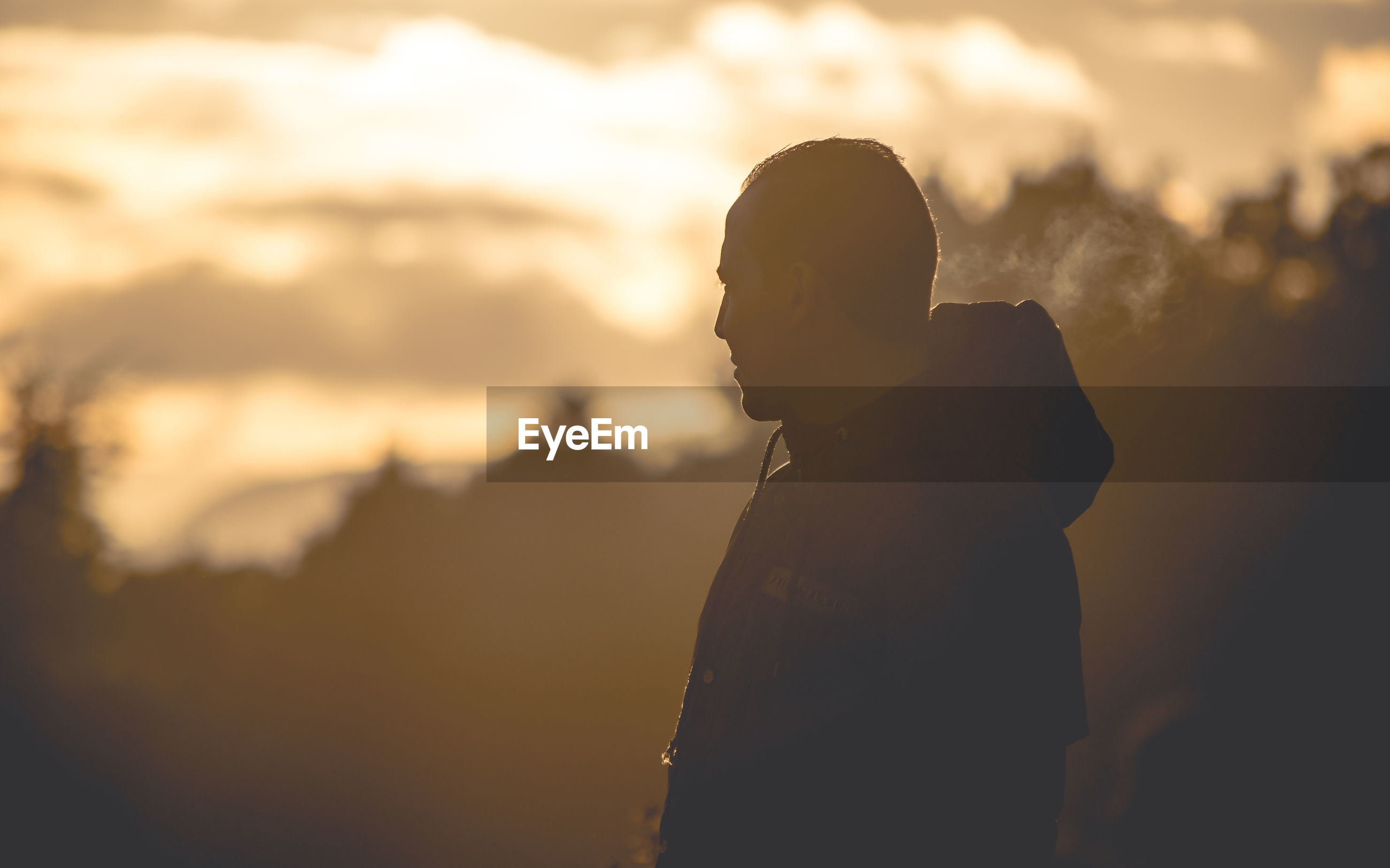 Side view of man standing against sky during sunset