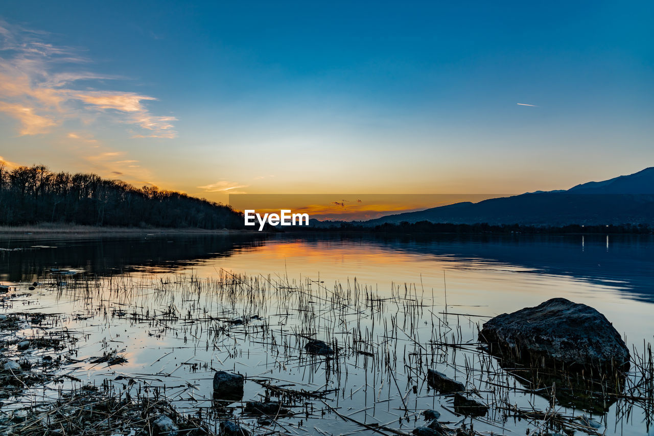 sky, sunset, scenics - nature, water, beauty in nature, tranquility, tranquil scene, lake, reflection, winter, cold temperature, non-urban scene, orange color, nature, snow, no people, cloud - sky, idyllic