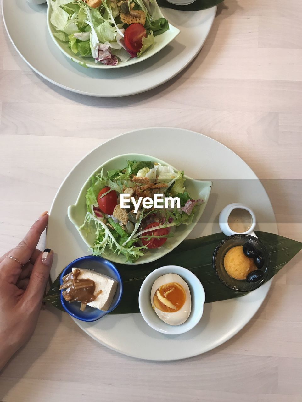 food and drink, food, table, human hand, hand, ready-to-eat, freshness, human body part, plate, one person, bowl, wellbeing, real people, healthy eating, indoors, high angle view, serving size, holding, unrecognizable person, meal, finger, crockery