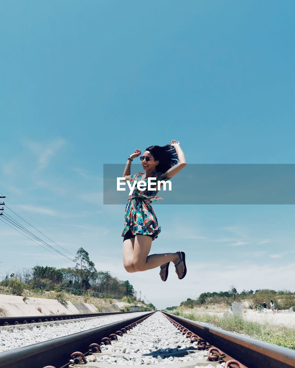 Full length of woman jumping in mid-air on railroad track against sky