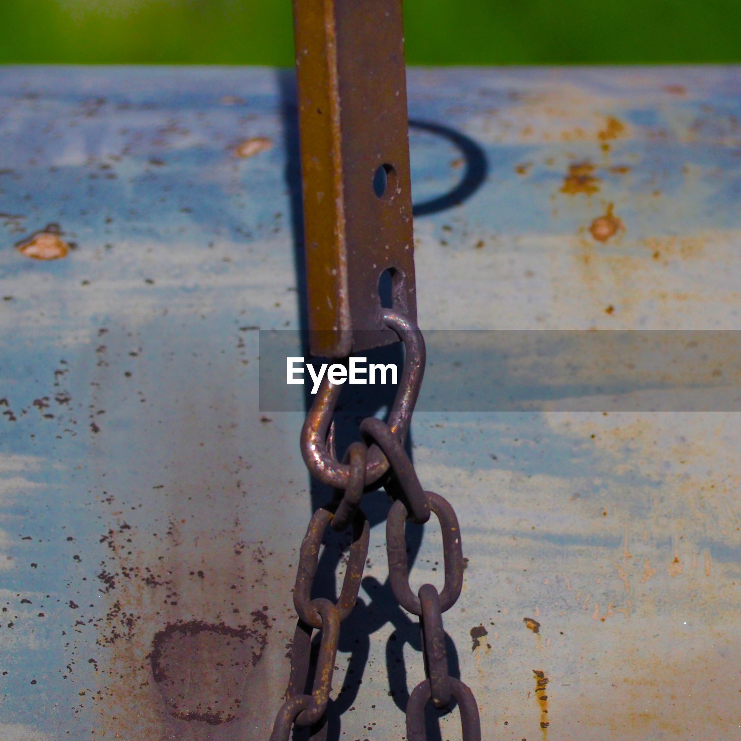 CLOSE-UP OF RUSTY METAL ON CHAIN