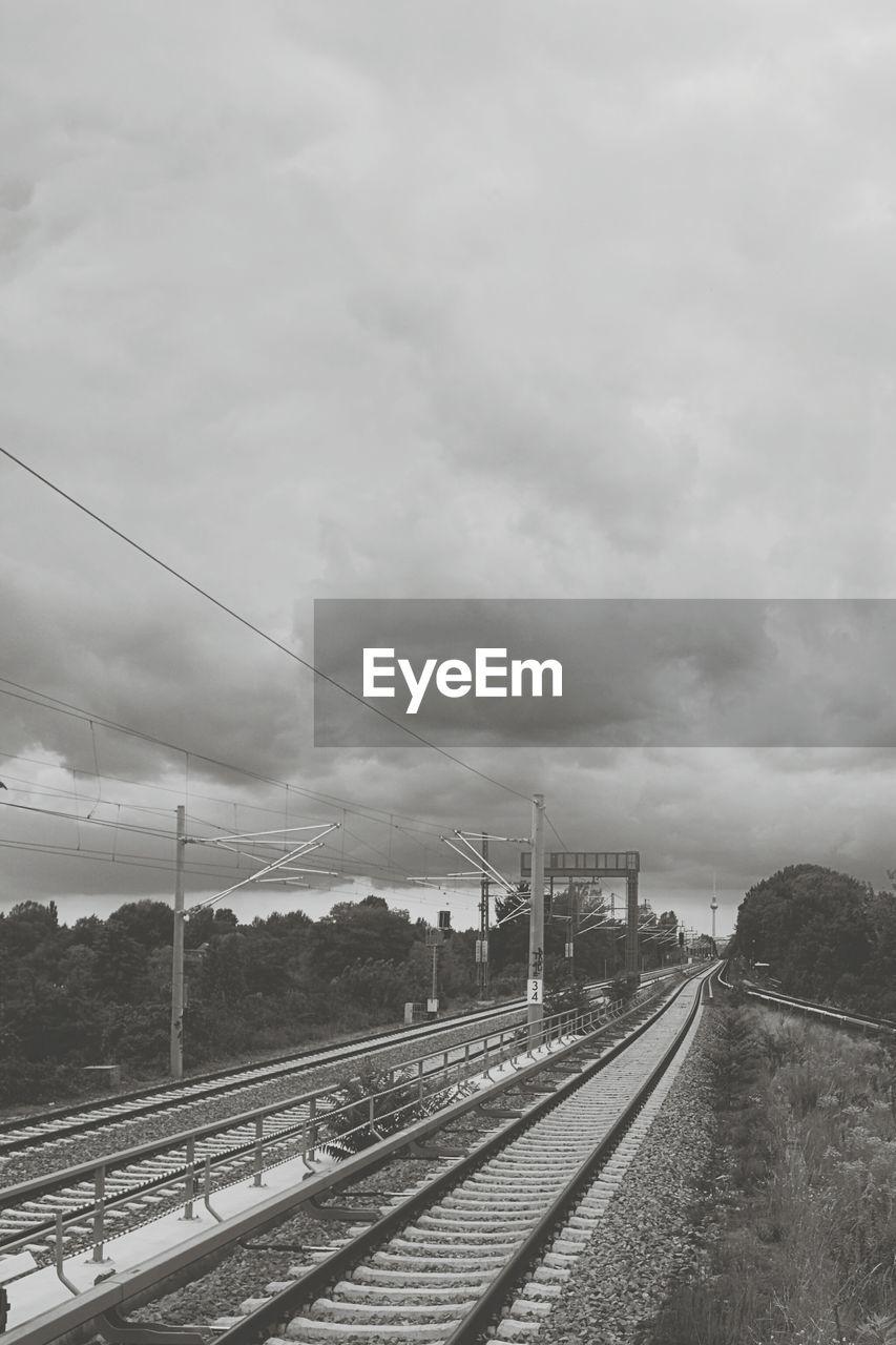 Railroad Tracks Against Cloudy Sky