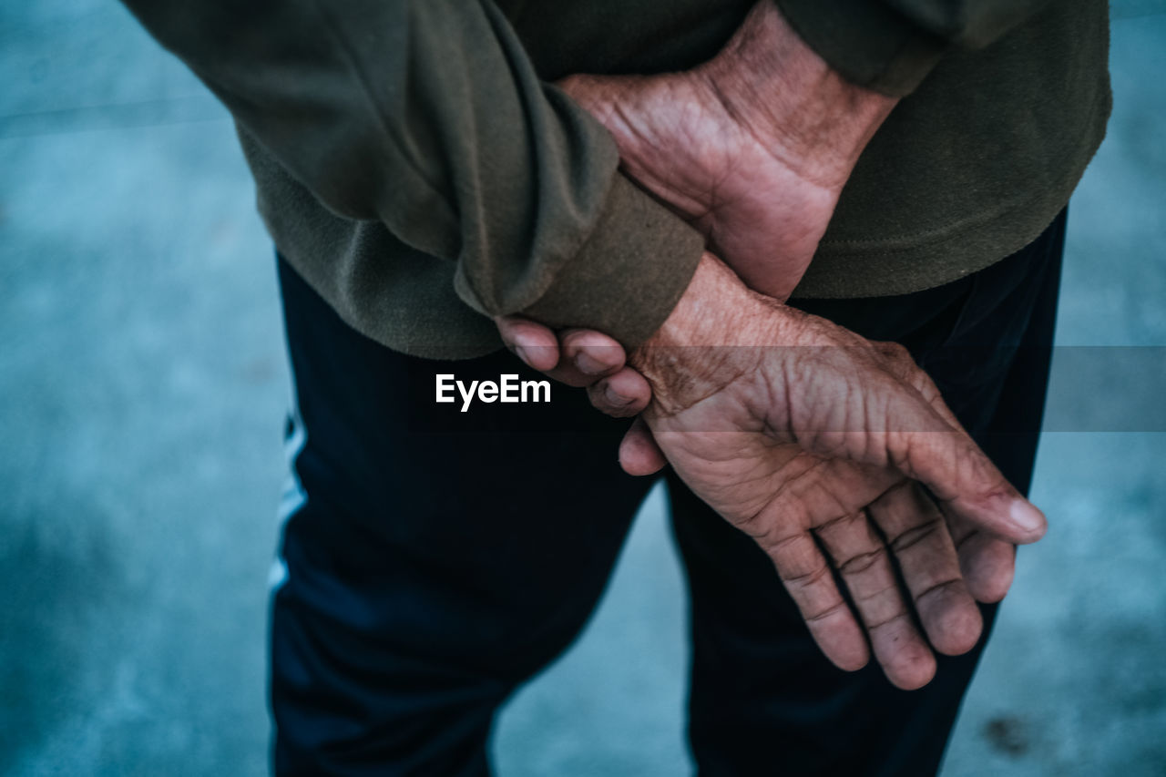 Close-Up Of Old Man's Hands Behind Back