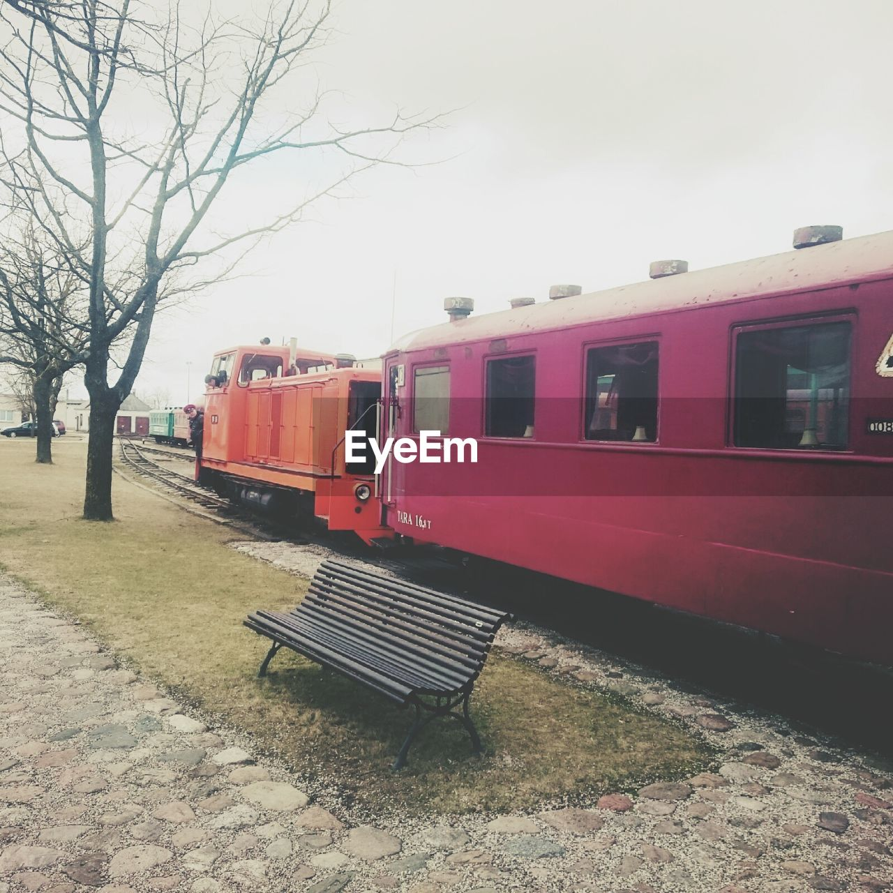 transportation, public transportation, train - vehicle, rail transportation, mode of transport, railroad station, railroad station platform, travel, railroad track, day, red, outdoors, no people, bare tree, sky