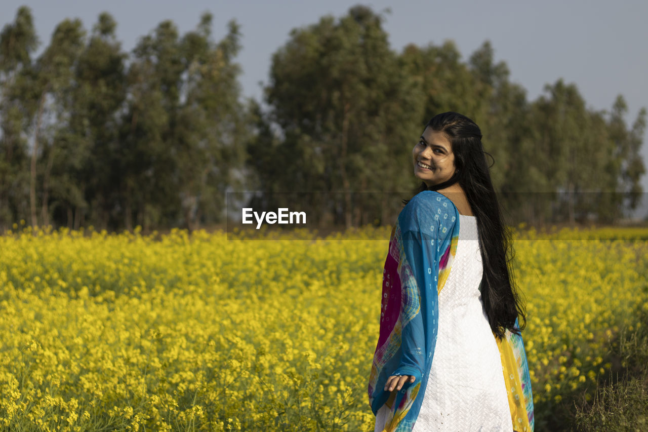 PORTRAIT OF BEAUTIFUL YOUNG WOMAN STANDING ON YELLOW LAND