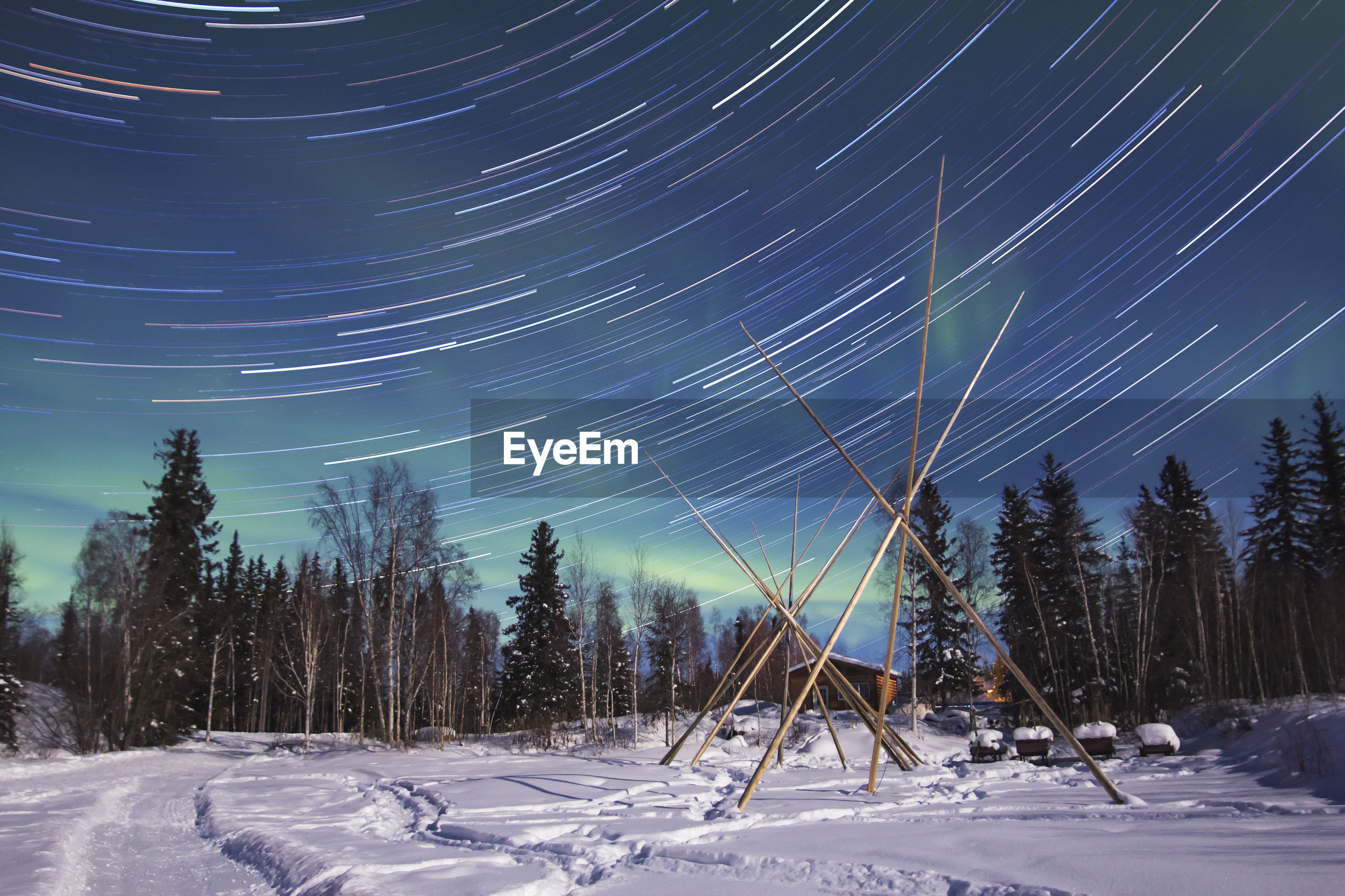 Star trail over landscape against sky