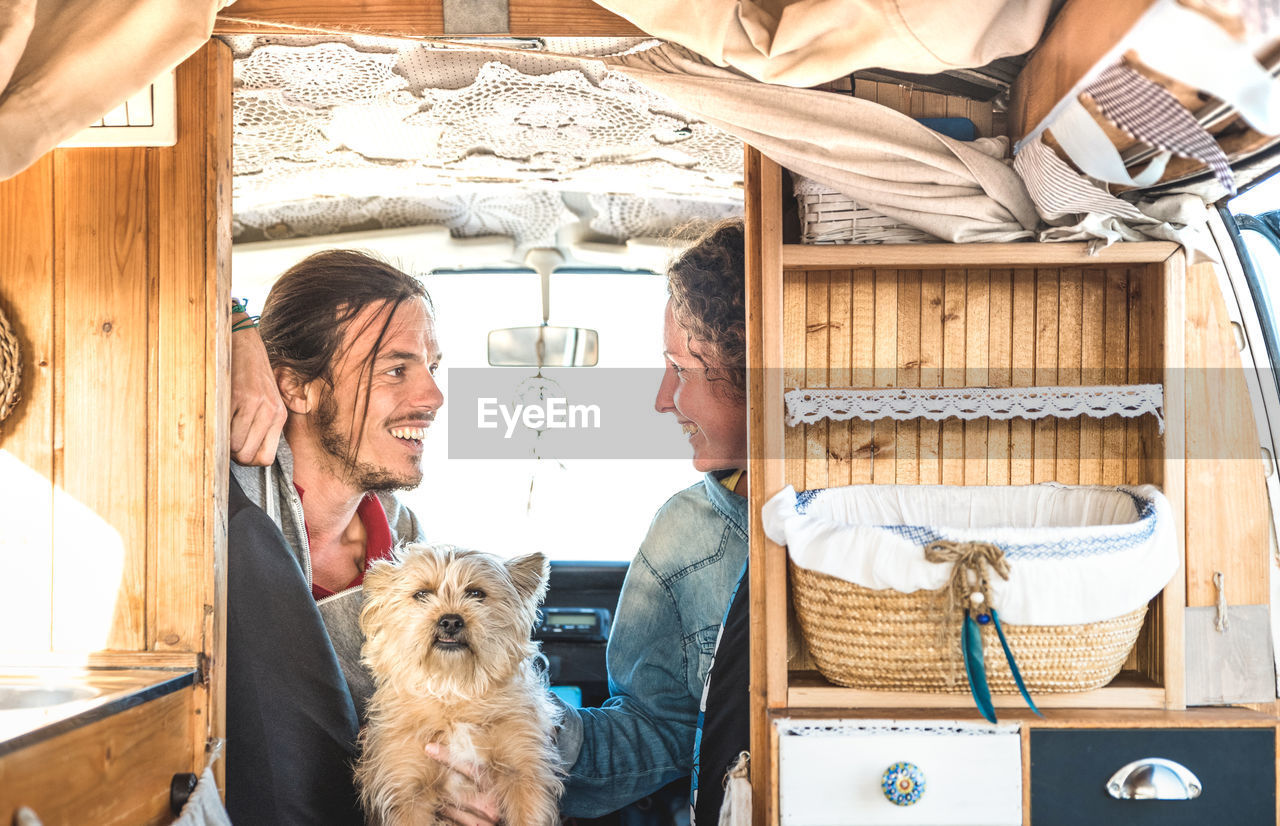 Happy couple with dog sitting in caravan