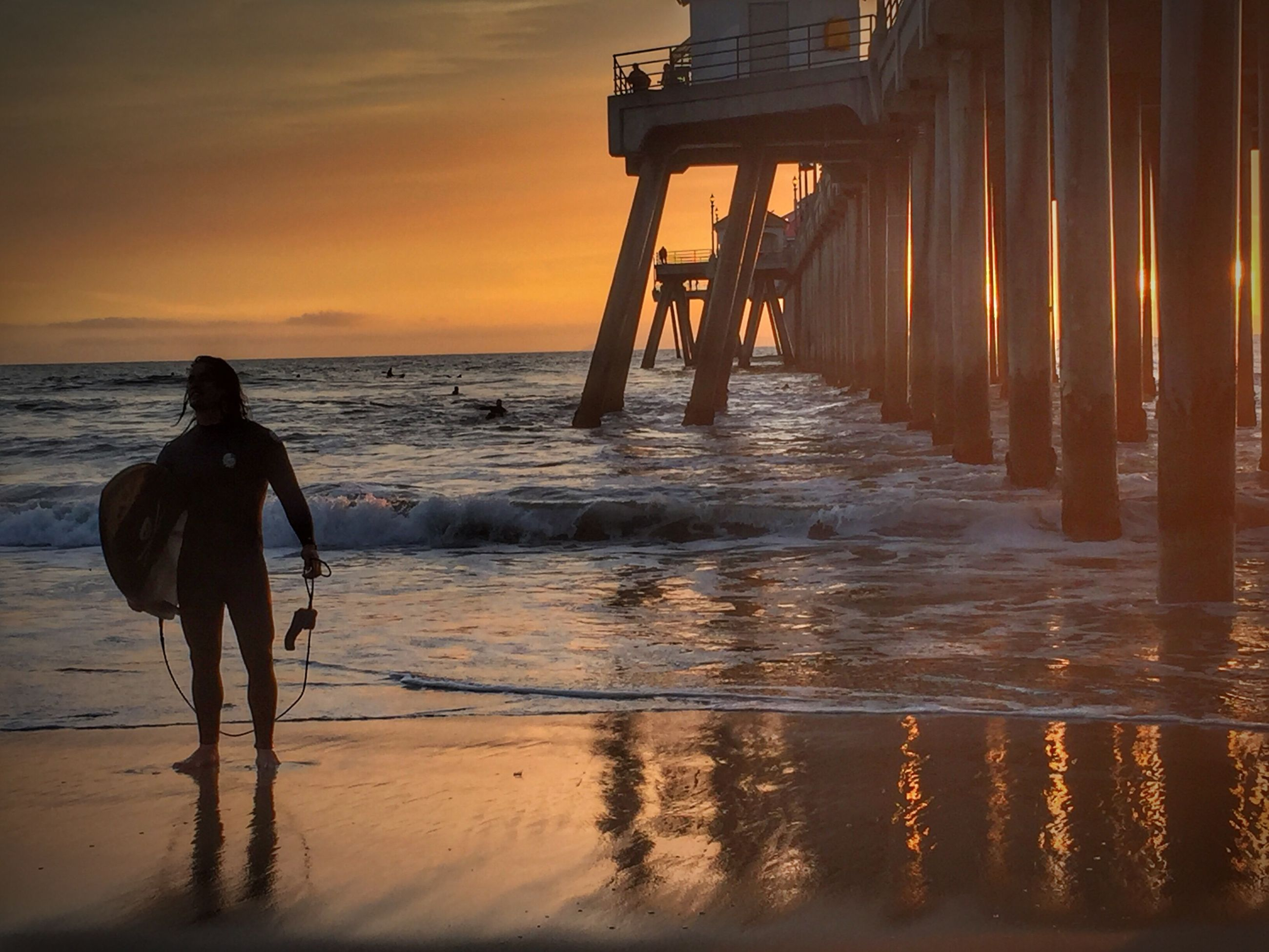 sunset, water, sea, beach, nature, real people, beauty in nature, standing, reflection, lifestyles, sky, leisure activity, scenics, sand, full length, one person, men, horizon over water, tranquility, outdoors, ankle deep in water, wave, women, day, people