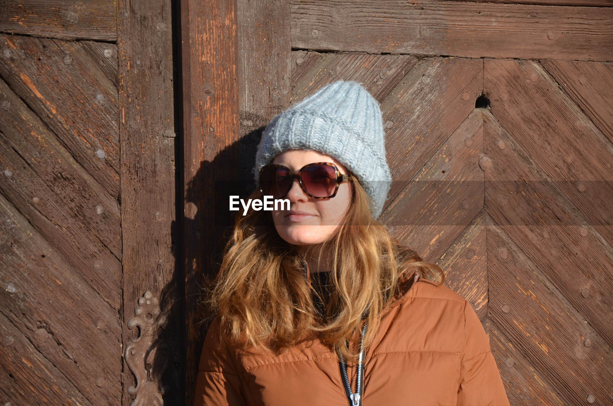 Woman wearing sunglasses while standing against wooden door