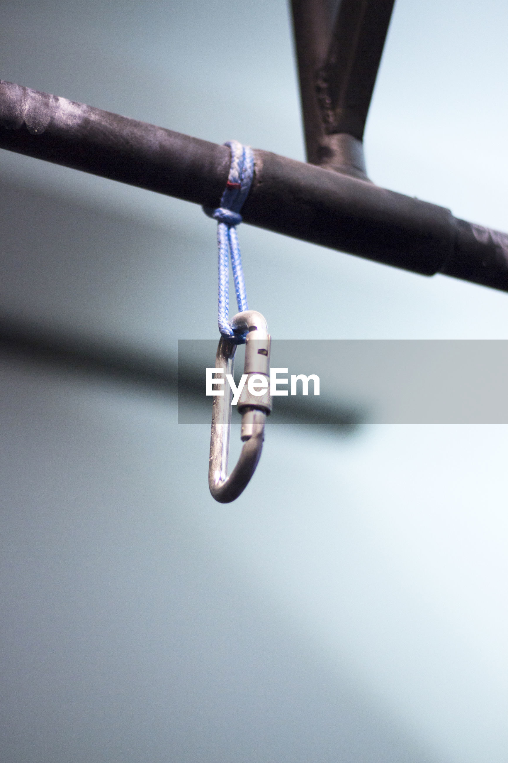Low angle view of carabiner hanging on rod