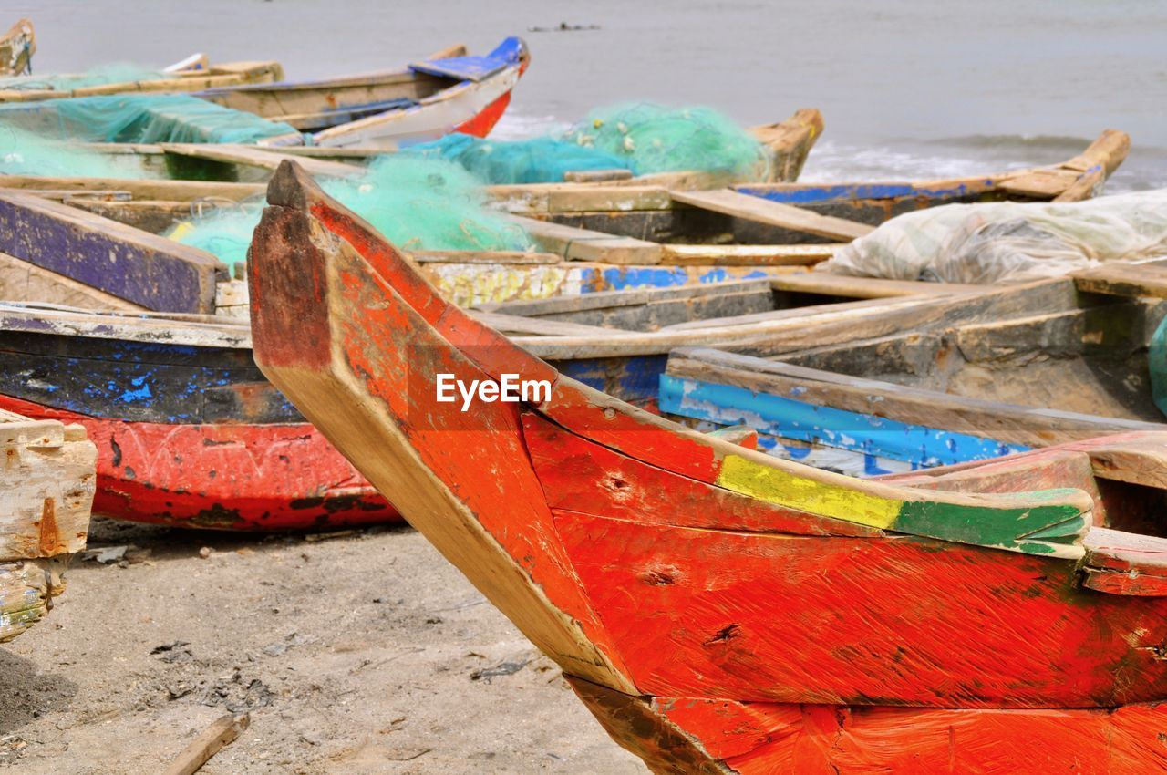 Fishing boats on sand against sea at beach